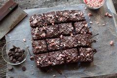 棒棒糖在土气木背景的正方形切的巧克力果仁巧克力 库存照片