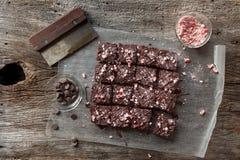 棒棒糖在土气木背景的正方形切的巧克力果仁巧克力 库存图片