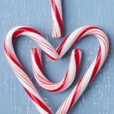 棒棒糖在蓝色木头的心脏标志集中了正方形 免版税图库摄影