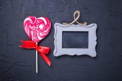 棒棒糖心脏和空的框架在黑织地不很细背景 免版税图库摄影