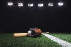 棒球、露指手套和棒在领域在光下在晚上 免版税库存照片