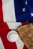 棒球和手套在一面美国国旗 库存图片