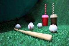 棒球和棒在绿草 免版税库存图片