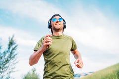 棒球帽、无线耳机和蓝色太阳镜快乐的微笑的跑的晚上奔跑和在手中举行的有胡子的人 免版税库存照片