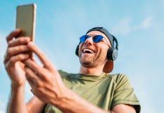 棒球帽、无线耳机和蓝色太阳镜的有胡子的人发现事滑稽在智能手机设备和快乐 免版税库存图片