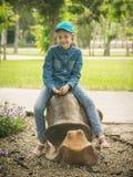棒球帽和牛仔布的女孩给在耳蜗的形状的骑马穿衣 免版税库存照片