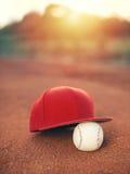 棒球帽和球在日落 免版税库存照片