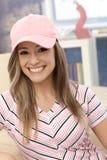 棒球帽微笑的运动的女孩 免版税库存照片