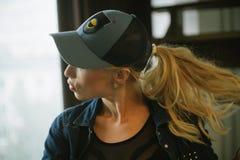 棒球帽的白肤金发的女孩 免版税库存图片