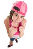 头戴棒球帽的滑稽的十几岁的女孩做赞许签字 库存照片