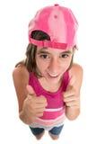 头戴棒球帽的滑稽的十几岁的女孩做赞许签字 免版税图库摄影