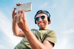 棒球帽,无线耳机和蓝色太阳镜快乐微笑的有胡子的人拍selfie照片使用现代 免版税库存图片