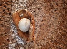 棒球手套和球在土织地不很细背景 免版税库存照片