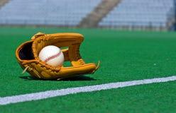 棒球手套和球在领域 图库摄影