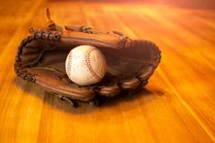 棒球有球的俘获器露指手套在木桌上 免版税图库摄影