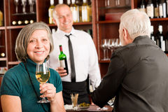 棒讨论男服务员的夫妇高级酒 免版税库存图片