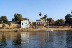 棕榈树包围的Nubian村庄的典型的白色房子在开罗埃及附近和在银行 图库摄影