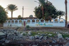棕榈树包围的Nubian村庄的典型的白色房子在开罗埃及附近和在银行 免版税库存图片