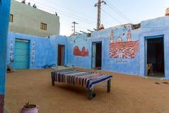 棕榈树包围的Nubian村庄的典型的白色房子在开罗埃及附近和在银行 库存图片