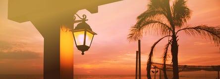 棕榈树和灯笼在日落 库存照片