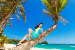 棕榈树的年轻美丽的亚裔女孩在一个热带海滩 库存图片