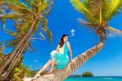 棕榈树的年轻美丽的亚裔女孩在一个热带海滩 免版税库存图片