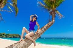 棕榈树的年轻美丽的亚裔女孩在一个热带海滩 免版税库存照片