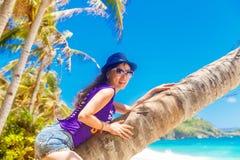 棕榈树的年轻美丽的亚裔女孩在一个热带海滩 免版税图库摄影
