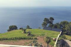 棕榈树陶器罐和照片太阳电池板在一个华美的大阳台有看法往海在巴尼亚尔武法尔马略卡 免版税库存图片