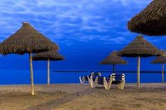 棕榈遮阳伞和海滩懒人在月光靠岸 免版税库存图片