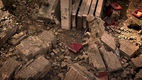 棕色伪装的走的战士横渡被毁坏的被放弃的砖瓦房,拿着自动炮,朝前看 影视素材