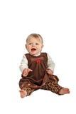棕色天鹅绒礼服的逗人喜爱的笑的婴孩 免版税库存图片