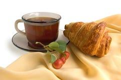 棕色新月形面包托起玻璃茶 免版税图库摄影