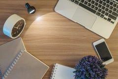 棕色木书桌特写镜头空间有光的从小灯在有被弄脏的计算机书和巧妙的电话的暗室构造了b 库存照片