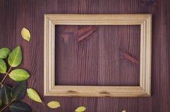 棕色木表面上的空的木制框架 免版税库存图片