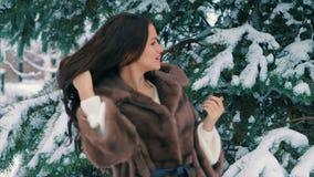 棕色毛皮深色的富有的妇女腰部外套在圣诞树慢动作背景的  股票录像
