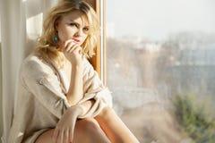 棕色毛线衣的年轻亭亭玉立的性感的妇女反对窗口 库存图片