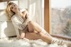棕色毛线衣的年轻亭亭玉立的性感的妇女反对窗口 免版税图库摄影