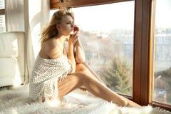 棕色毛线衣的年轻亭亭玉立的性感的妇女反对窗口 免版税库存照片