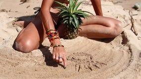 棕色泳装的性感的妇女在与菠萝图画的海滩在沙子 在a的年轻女性享用的暑假 影视素材