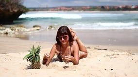 棕色泳装的性感的妇女在海滩用菠萝 在热带巴厘岛的年轻女性享用的暑假 股票录像
