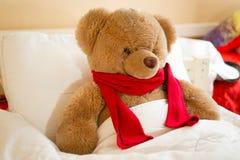 棕色玩具熊特写镜头在床上的红色围巾的 库存照片