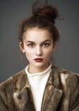 棕色皮大衣姿势的时尚妇女 免版税库存图片