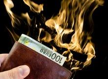 给从棕色皮革钱包的贿款有与被隔绝的灼烧的火的一百欧元的 库存照片