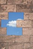 棕色砖墙细节  在蓝天的一朵云彩是在它后 免版税库存图片