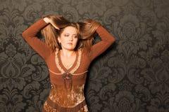 棕色礼服常设墙壁妇女 库存照片