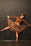 棕色礼服常设墙壁妇女 免版税库存图片