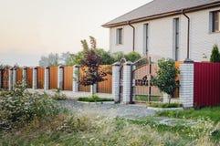 棕色篱芭由polyprofile制成与在一个现代样式与砖专栏,乡间别墅的设计的一个机盖 库存照片