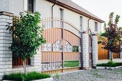 棕色篱芭由polyprofile制成与在一个现代样式与砖专栏,乡间别墅的设计的一个机盖 免版税图库摄影