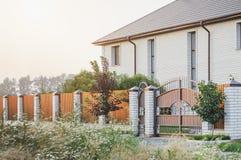 棕色篱芭由polyprofile制成与在一个现代样式与砖专栏,乡间别墅的设计的一个机盖 免版税库存图片
